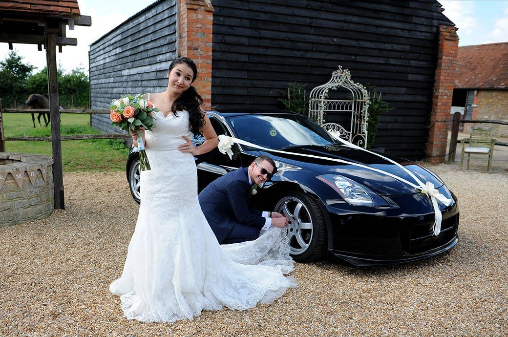 Hilarious and unusual wedding photo of the Groom polishing his treasured car alloys with his wife's wedding dress at the lovely Clock Barn Hall in Godalming Surrey