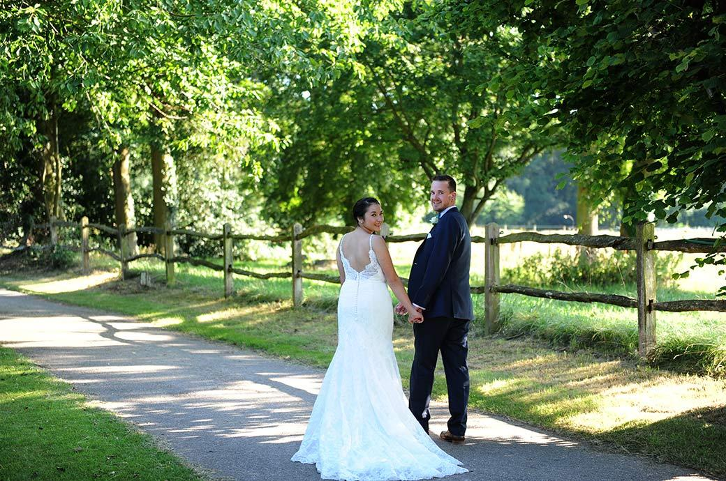 Relaxed handsome wedding couple look back at the Surrey Lane wedding photographer at Clock Barn Hall Godalming as they walk off down the lane for some romantic photos