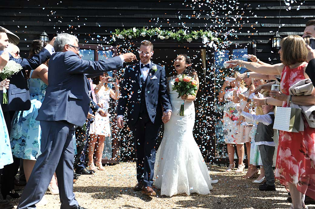All smiles in this fun wedding picture taken at Surrey wedding venue Clock Barn Hall in Godalming as the newlyweds get covered in a shower of brightly coloured confetti