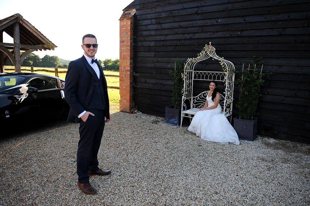 Smiling Groom standing with hand in pocket in foreground at the Clock Barn Hall wedding venue in Surrey whilst his Bride sits in an ornamental garden chair in the background