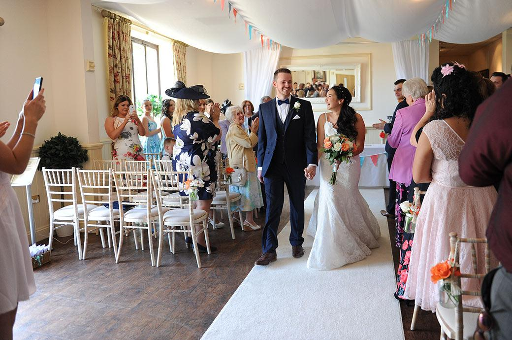 Lovely joyful wedding picture of the happy couple as they walk hand in hand down the aisle at Surrey wedding venue Clock Barn Hall now as husband and wife