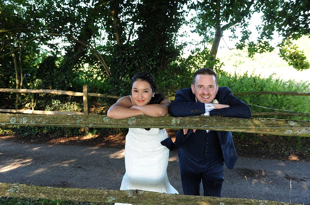 Cross armed and leaning on a country fence overlooking a field the happy newlyweds at the delightfully rural Clock Barn Hall in Surrey enjoy their time out from the wedding reception