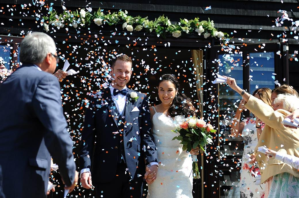 Young handsome newlywed couple smile outside the Ceremony Room at Surrey wedding venue Clock Barn Hall as they feel the shower of confetti cover them