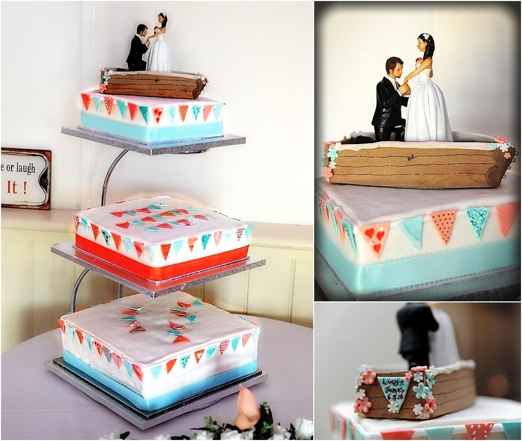 Surrey wedding venue Clock Barn Hall reception photograph of a three tier wedding cake with colourful pendant decoration and an amusing groom proposing in a boat cake topper
