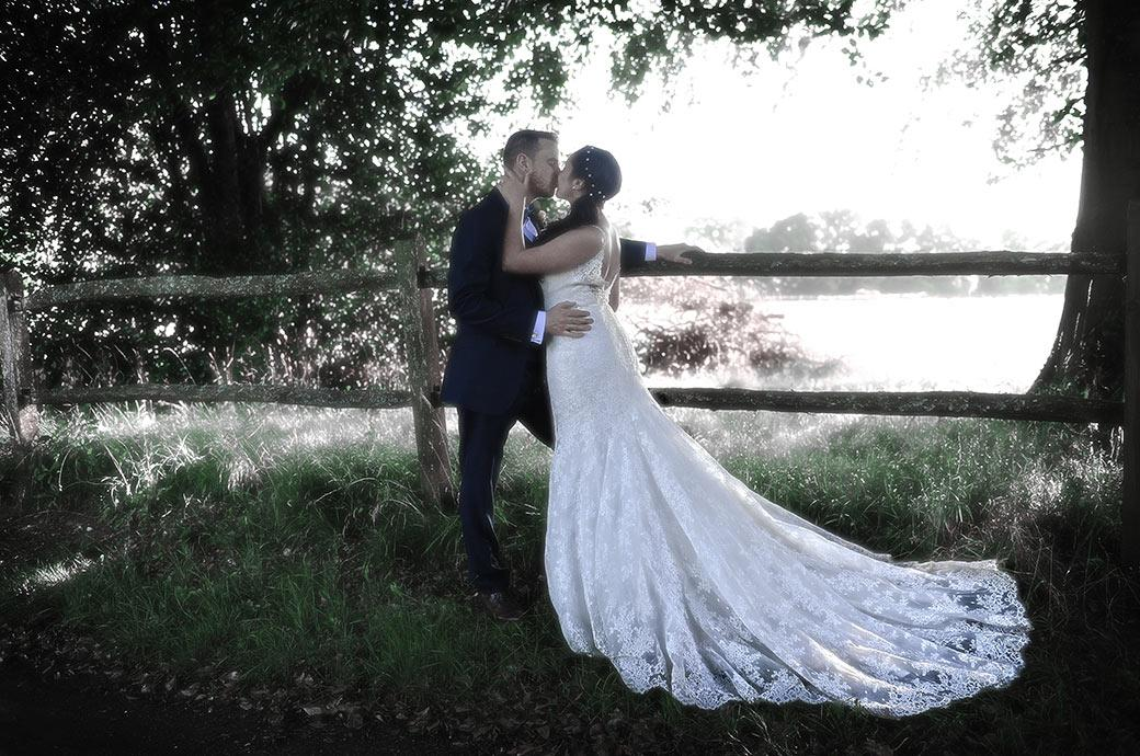 Tender romantic kiss between a Bride and Groom standing on a lane by a fence overlooking a field at the beautifully rural and peaceful Clock Barn Hall Surrey wedding venue