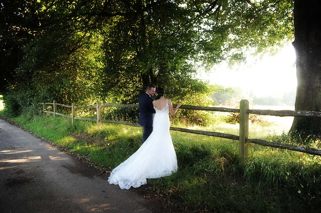 An intimate moment between the Bride and groom captured as they stand on a lane by a fence overlooking fields at the lovely rural Surrey wedding venue Clock Barn Hall in Godalming