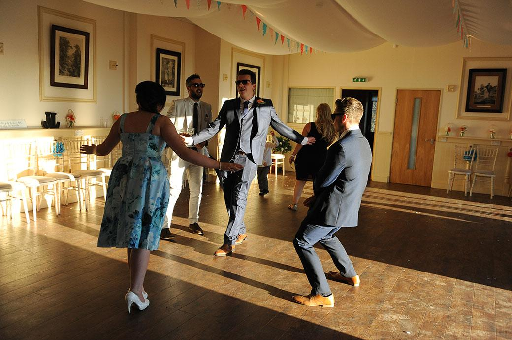 As the DJ warms up guests get started on the dancefloor captured in the glorious evening sunshine through the open doors at Clock Barn Hall in the beautiful Surrey countryside