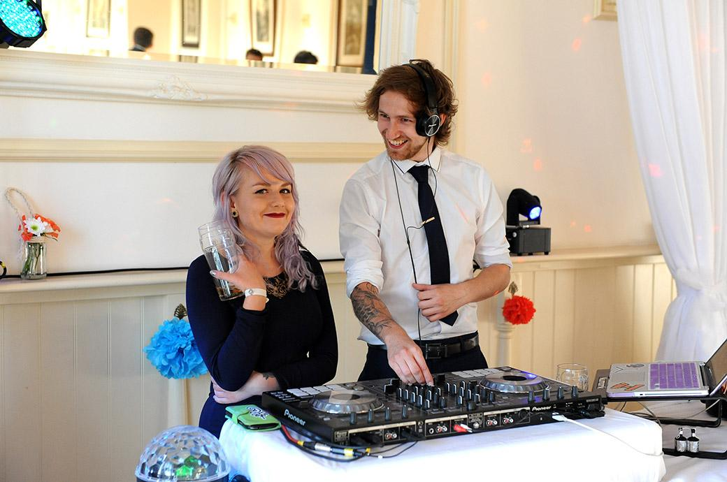 All fun and smiles captured in this wedding photo of  the DJ and partner as they get the music going for the Clock Barn Hall wedding reception at in the lovely countryside of Godalming Surrey