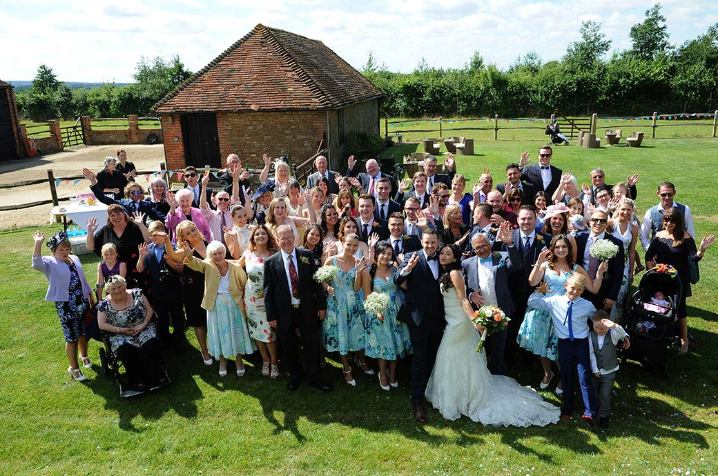 Newlyweds with family and guests on the lawn at Clock Barn Hall Godalming Surrey waving to the Surrey Lane wedding photographers for the everyone group photo