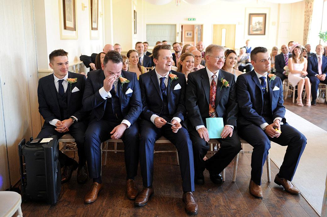 Smiles laughter and emotion captured in the front row of the ceremony room at the lovely Surrey wedding venue Clock Barn Hall in the Godalming countryside