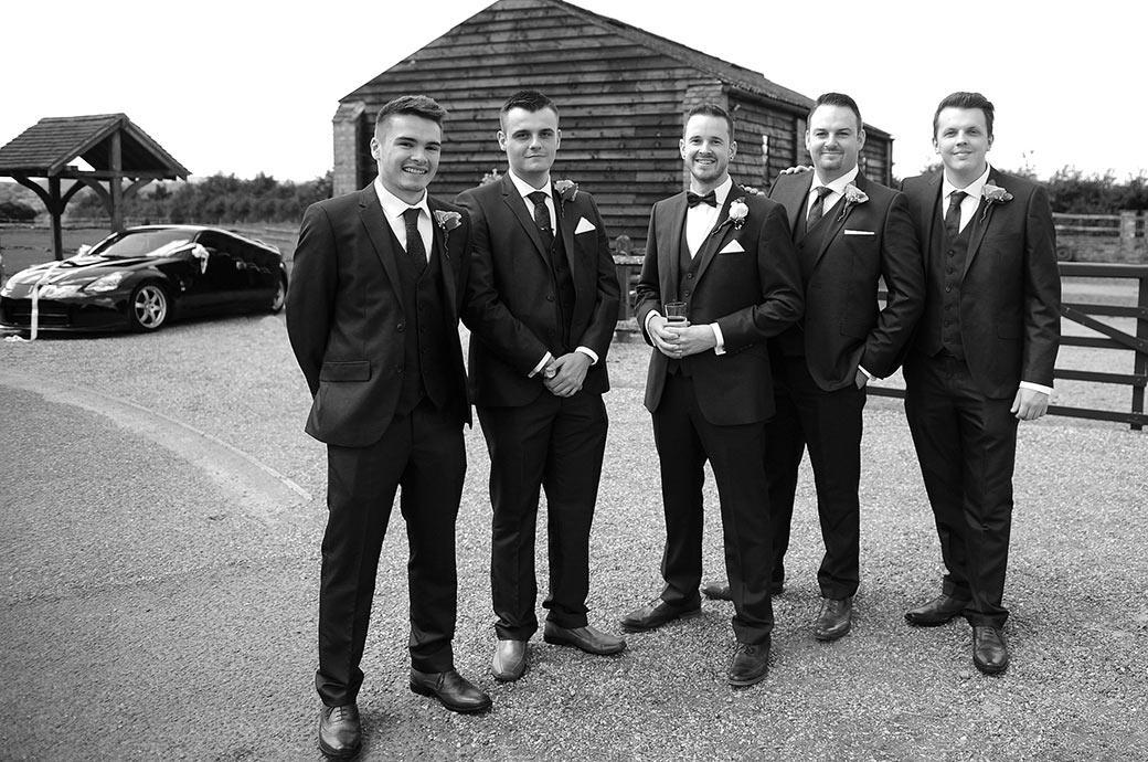 Relaxed and smiling Groom stands in the yard at the lovely Clock Barn Hall in the Surrey countryside flanked by his groomsmen as they await to greet family and guests