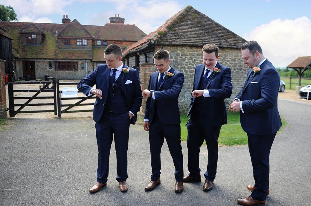 Groomsmen have fun as they check their watches for the late bride captured at Clock Barn Hall a lovely tranquil Surrey wedding venue in Godalming