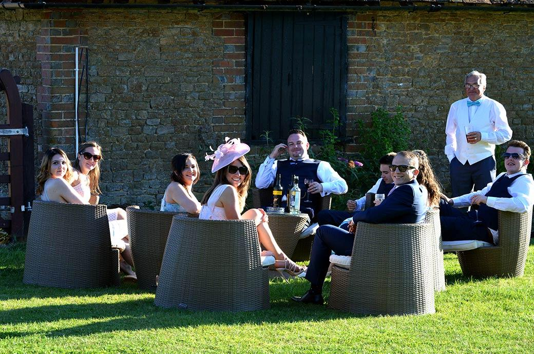 Smiling and relaxed wedding guests sitting on rattan chairs in the afternoon sun look over towards activities on the lawn at the delightful rural Clock Barn Hall in Surrey