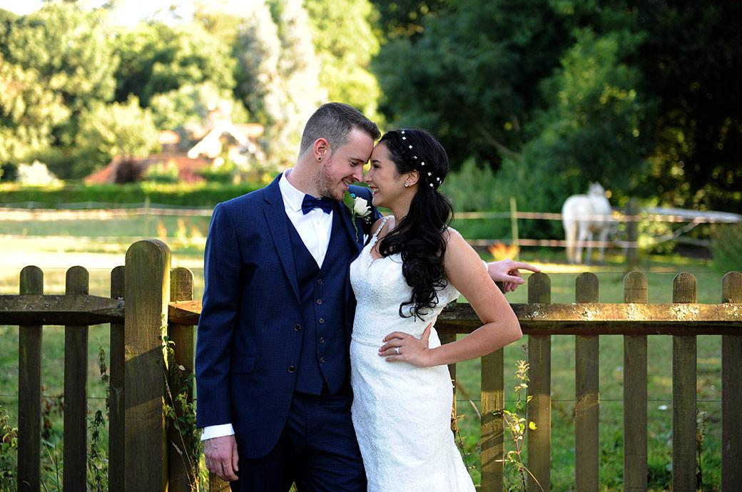 Lovely romantic wedding picture of  newlyweds pressing their heads together at the rural Surrey wedding venue Clock Barn Hall with fields and a white horse in the background