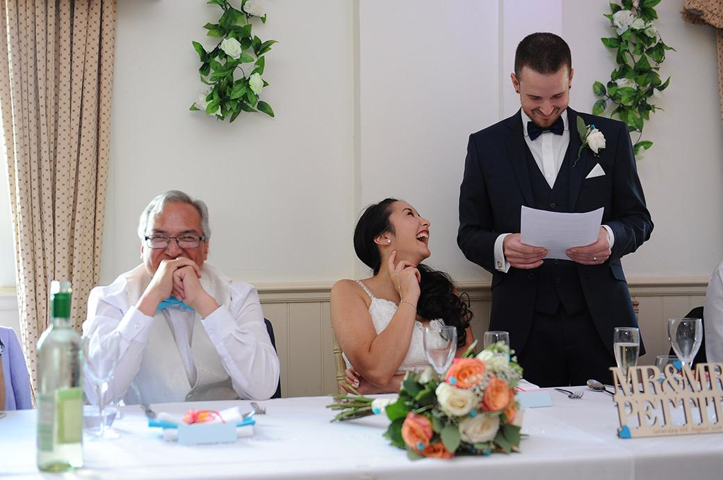 Bride and father captured in this wedding photo taken at Surrey wedding venue Clock Barn Hall Godalming as they laugh during the funny Groom's wedding speech