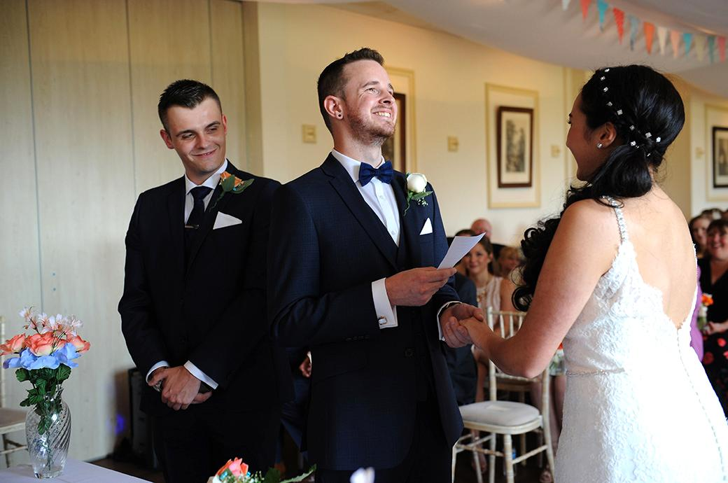 Smiles and emotion captured in this wedding picture taken at Clock Barn Hall Godalming Surrey as the Groom holds his Bride's hand and says his marriage vows