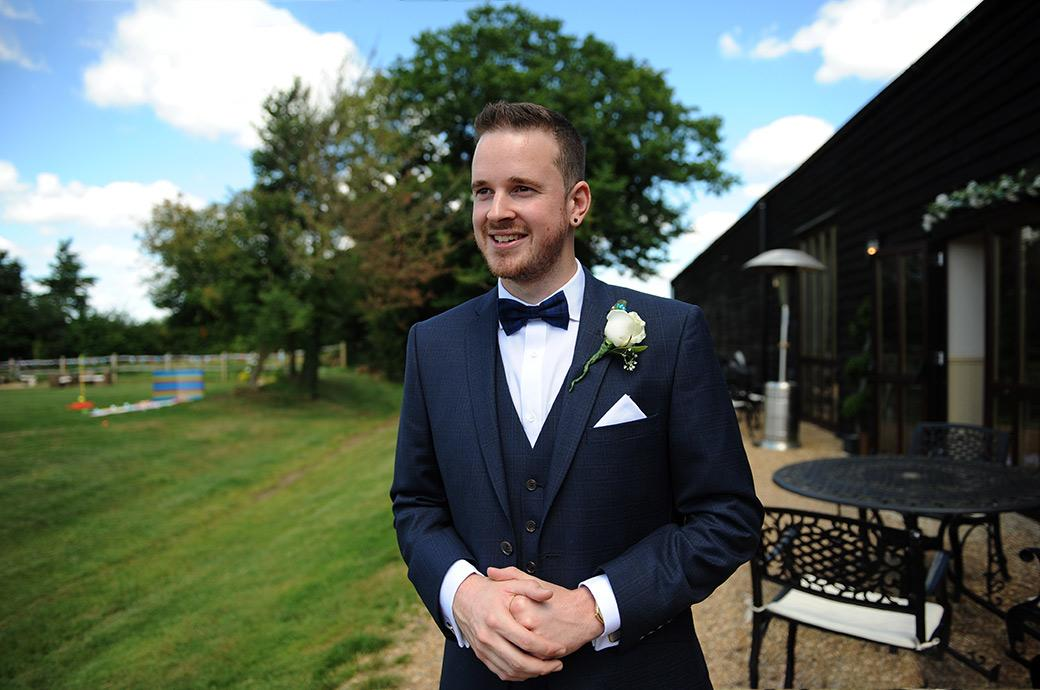Handsome and slightly nervous groom in this wedding picture taken while waiting outside the lovely rural Surrey wedding venue Clock Barn Hall ready to greet the arriving guests