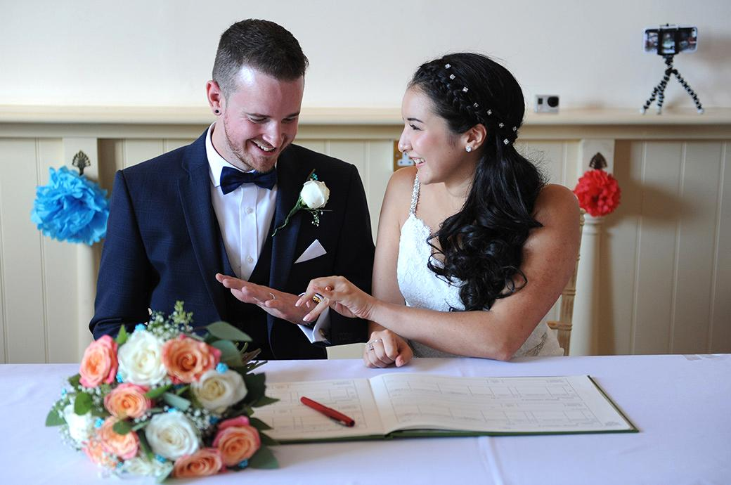 Smiles of happiness as the Bride and Groom share a precious moment as they look at each others wedding rings at the delightful Surrey wedding venue Clock Barn Hall