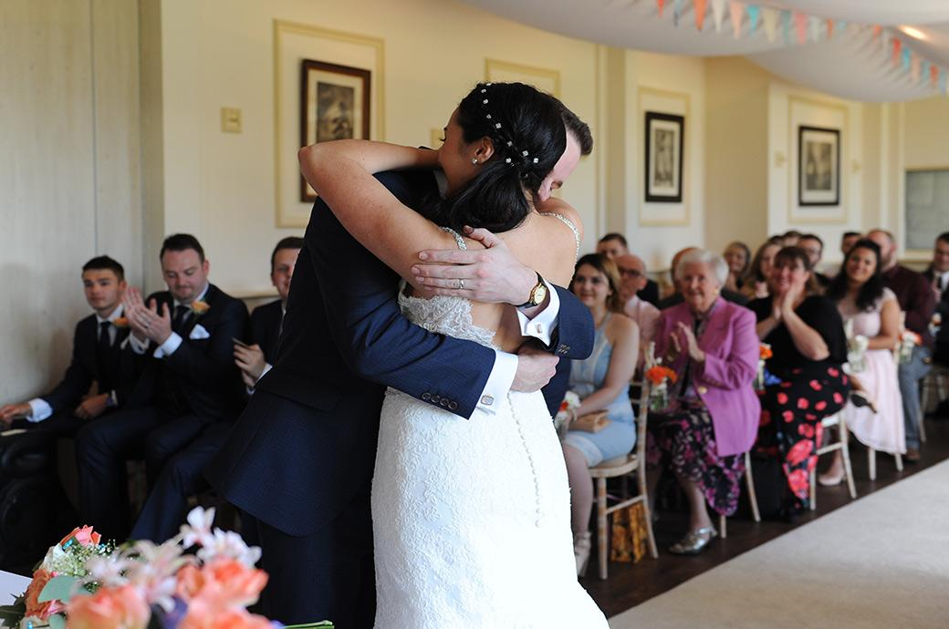 Sweet and touching hug of joy for the newlyweds at the Clock Barn Hall wedding venue in Godalming Surrey as they are announced husband and wife