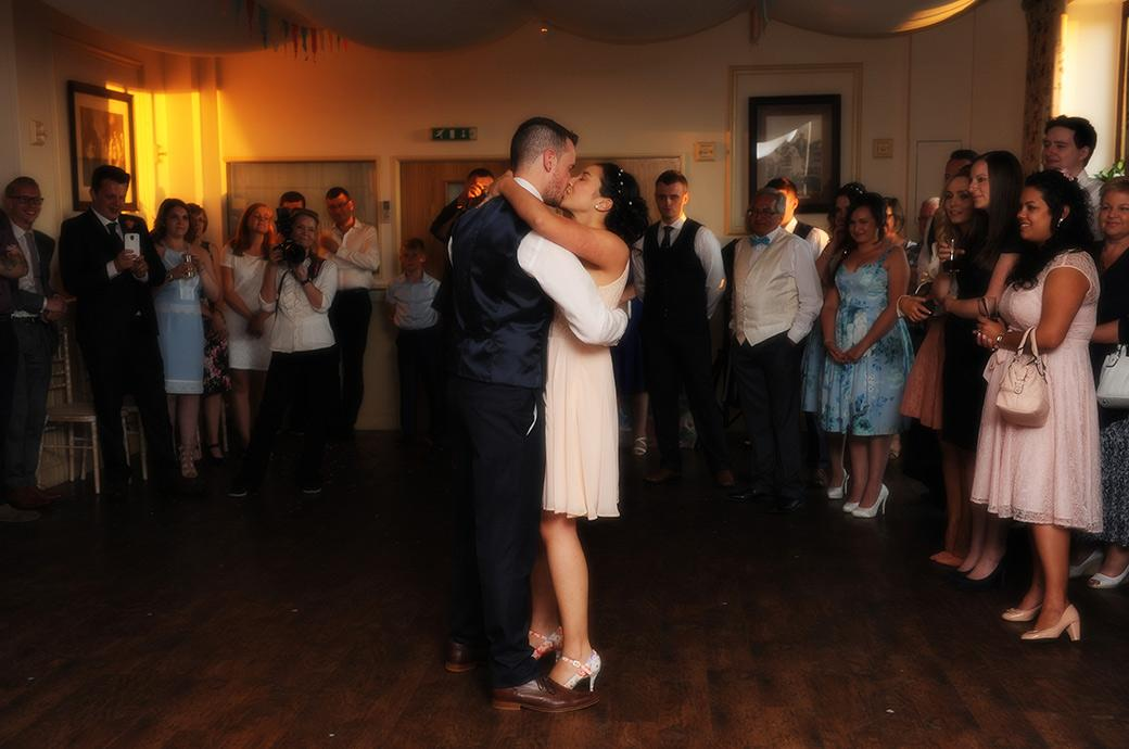 Newlywed couple romantically kiss in front of everyone on the dancefloor during their first dance at the wonderful rural Surrey wedding venue Clock Barn Hall
