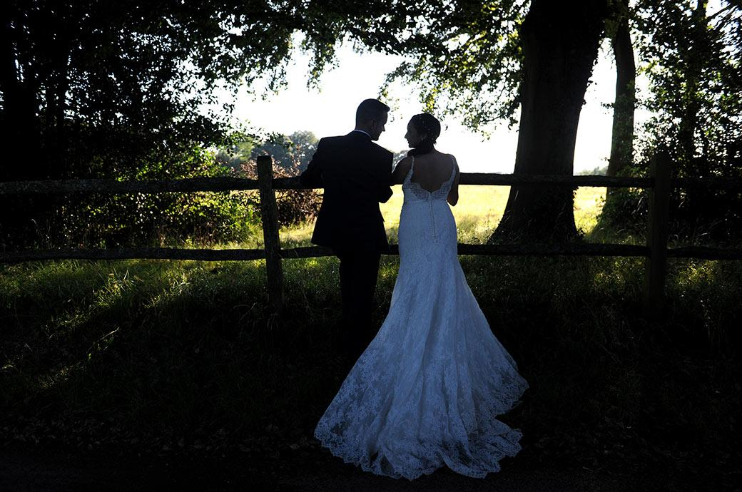 Intimate silhouette wedding picture of a newlywed couple at Clock Barn Hall Godalming in Surrey talking to each other as they lean on a wooden fence off a lovely country lane