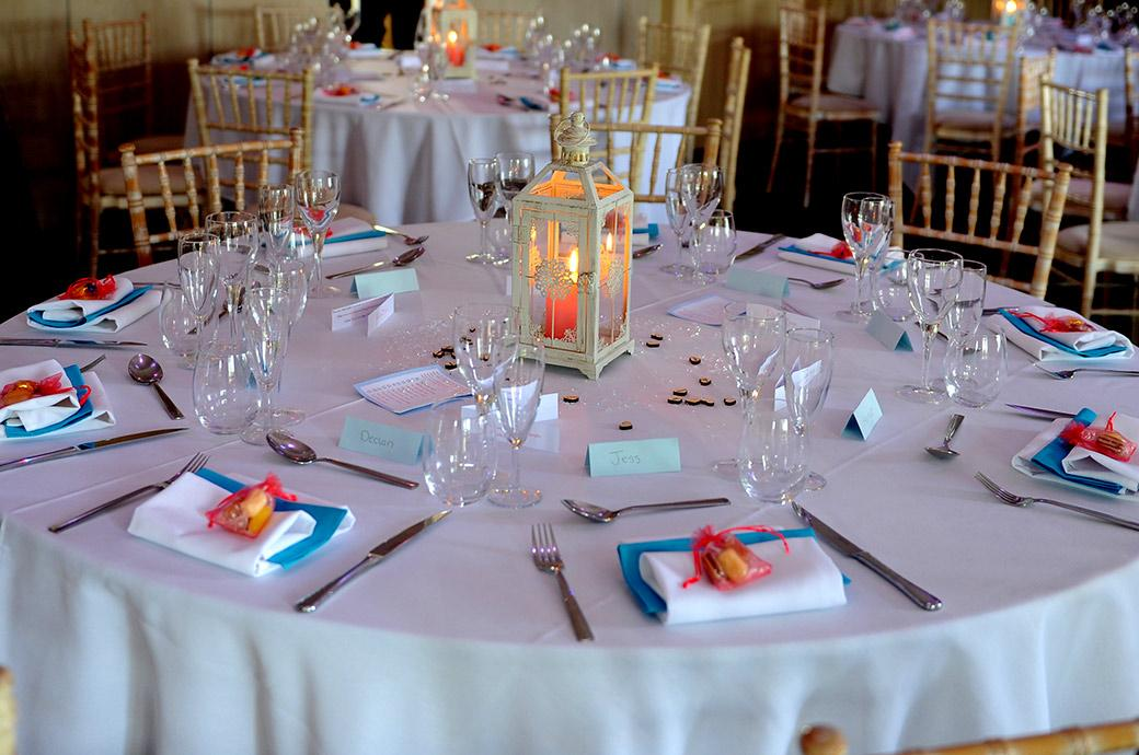 Colourful and informal table settings in blue red and orange are the order of the day for the  Clock Barn Hall wedding breakfast in Godalming Surrey