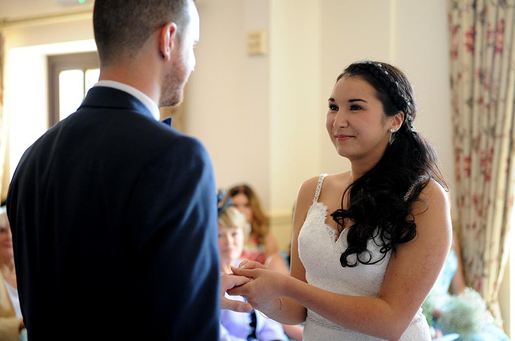 A smiling Bride looks into the eyes of the Groom as she hold the wedding ring on his finger captured at Clock Barn Hall Godalming a rural wedding venue in Surrey
