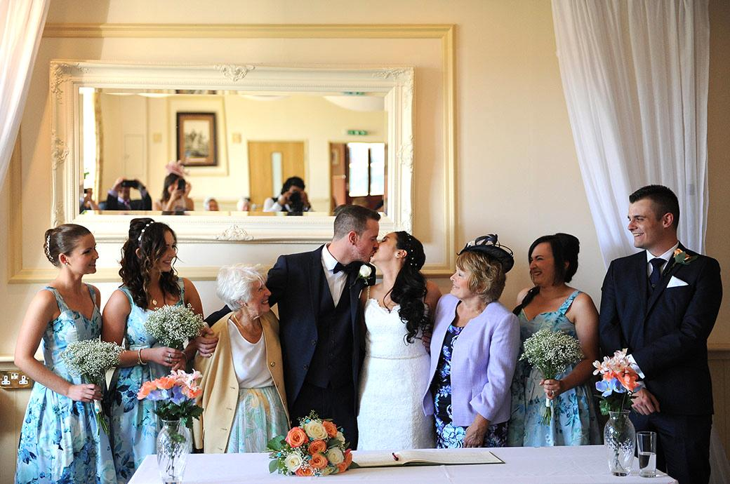Newlyweds kiss as their mothers and the Bridesmaids and best man look on captured in this lovely photo taken at Clock Barn Hall Godalming by Surrey Lane wedding photographers