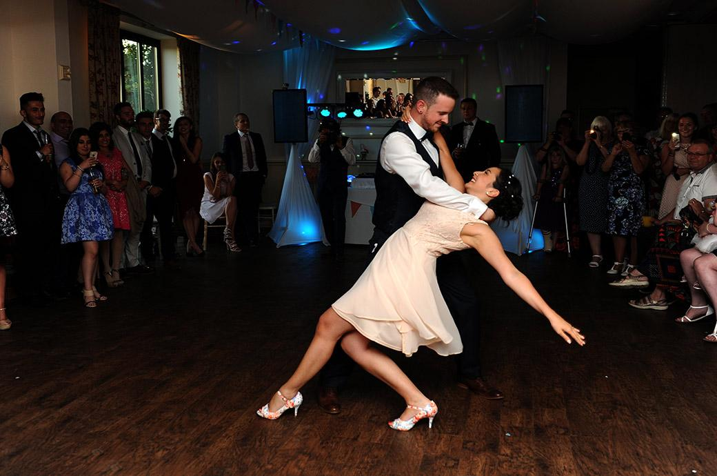 Bride and Groom demonstrate their previous dancing pedigree as they perform for their first dance in this impressive Clock Barn Hall wedding photo taken in Godalming Surrey