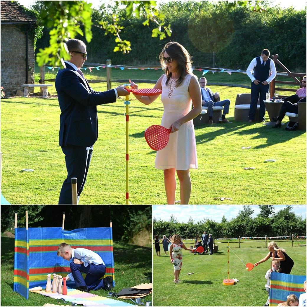 Guests having fun in these wedding pictures as they play skittles and Swing ball out on the lawn during the reception drinks at Surrey wedding venue Clock Barn Hall Godalming