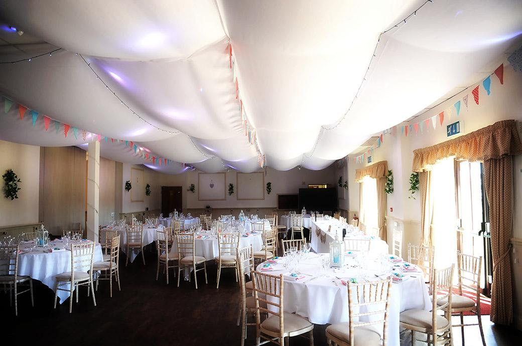 The  reception room in Clock Barn Hall in rural Surrey dressed for the wedding breakfast and complete with wicker chairs white billowing sheets and lightly coloured pendant flags