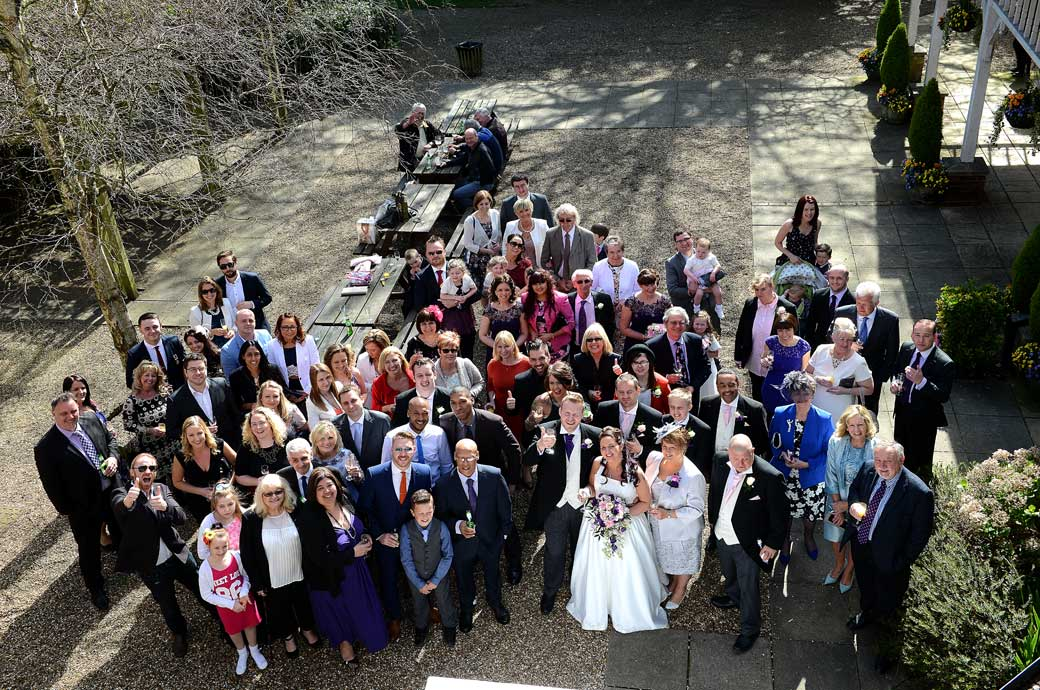 The terrace at Coulsdon Manor provides the perfect place for a classic everyone at the wedding picture when the Surrey Lane wedding photographer takes it from the roof above