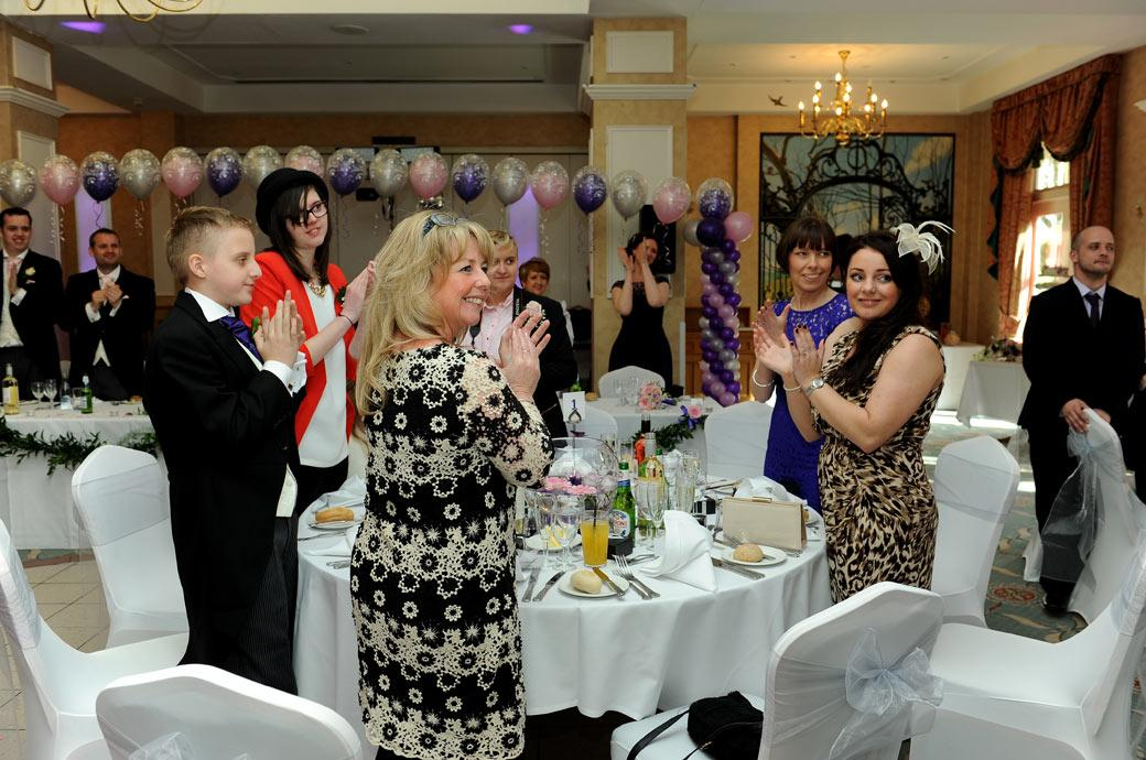 Smiling guests stand and applaud in this wedding picture at the arrival of the bride and groom at the  Manor House Suite Coulsdon Manor for the wedding breakfast
