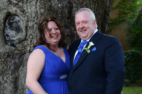 Smiling newlyweds in blue standing by a great old tree in this wedding picture taken in the grounds of Coulsdon Manor a Surrey wedding venue with a golf club