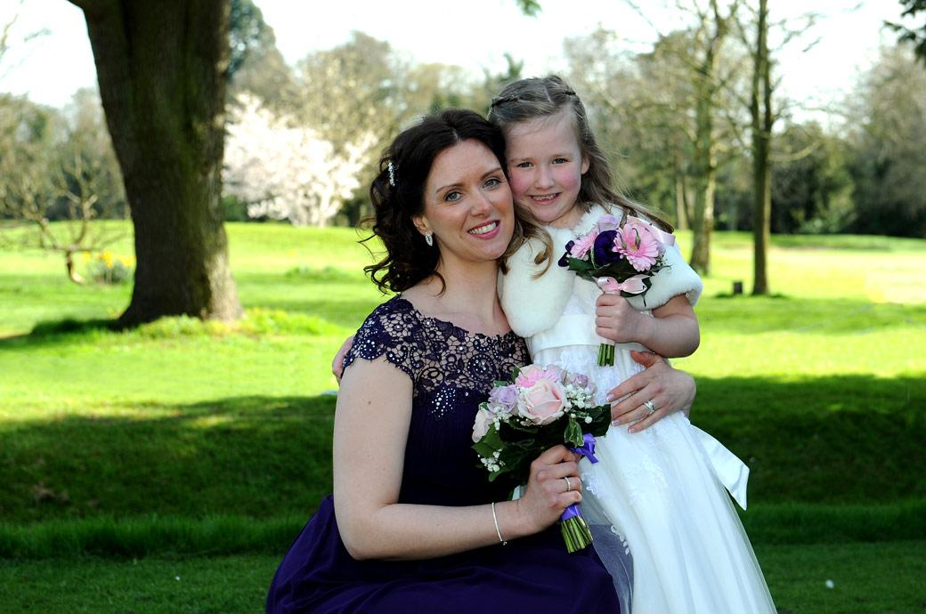 Bridesmaid has a wedding photo with her flower girl daughter out on the lawn at the tranquil and relaxed Surrey wedding venue Coulsdon Manor