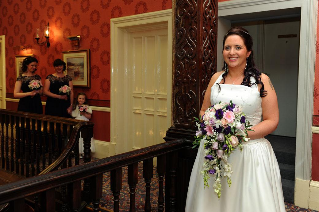 A smiling Bride waits on the stairs waiting to be called to The Blenheim Suite in this sweet wedding photograph taken at Coulsdon Manor by a Surrey Lane wedding photographer