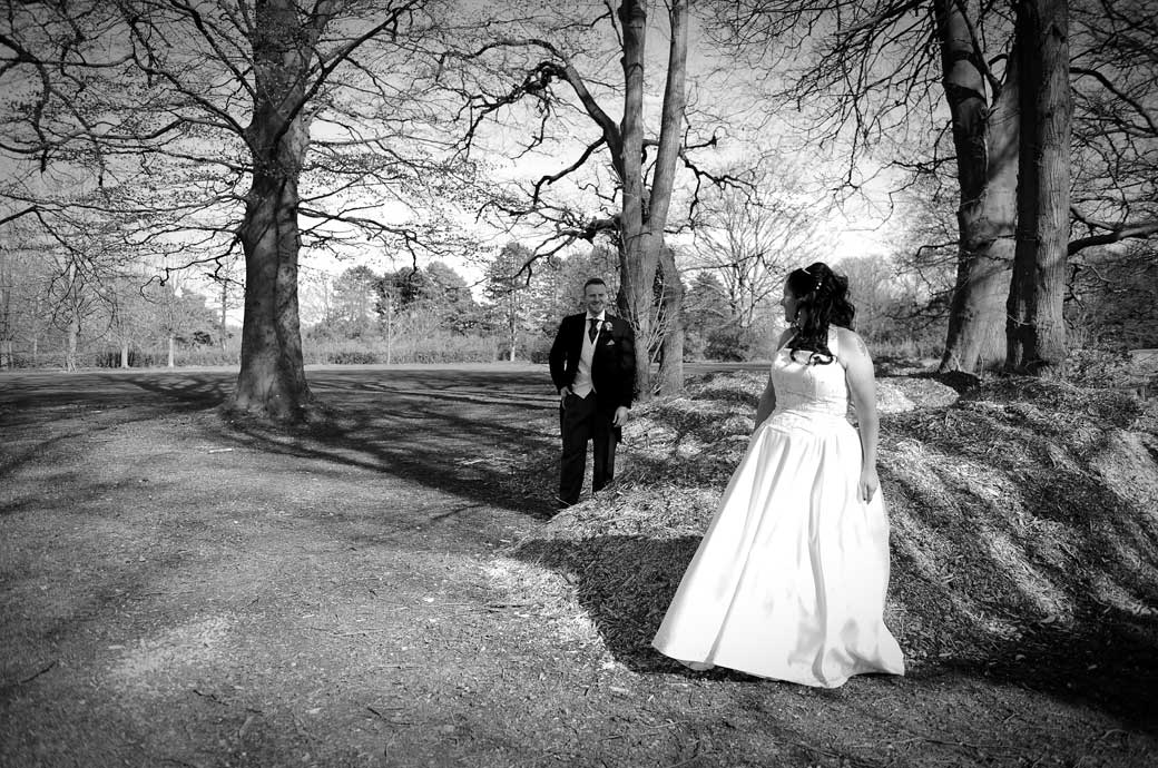 Bride looks over to her smiling husband as they stand in the woods near a woodpile captured in this Surrey wedding photo by the golfing fairway at Coulsdon Manor