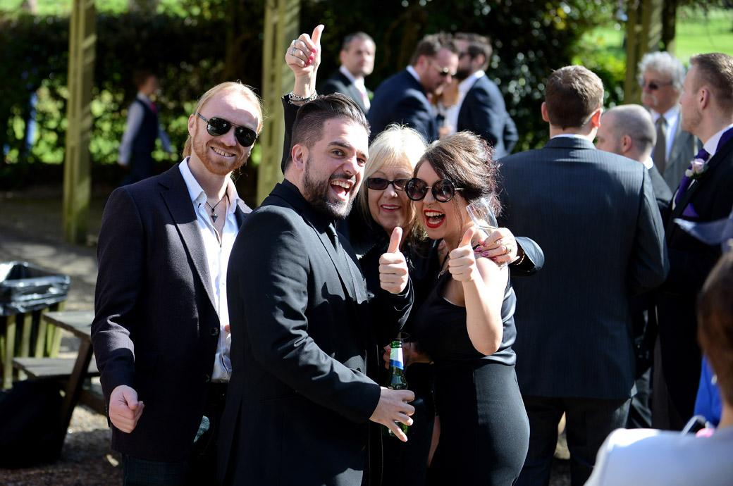 Guests give the Surrey Lane wedding photographer the thumbs up in this fun wedding photo captured at Coulsdon Manor by Surrey Lane wedding photographers