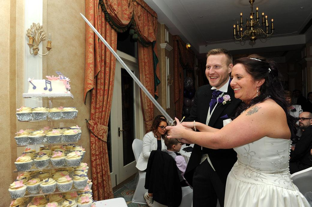 Smiling newlyweds get ready to cut their wedding cake with a sword captured in The Manor House Suite at Coulsdon Manor by a Surrey Lane wedding photographer