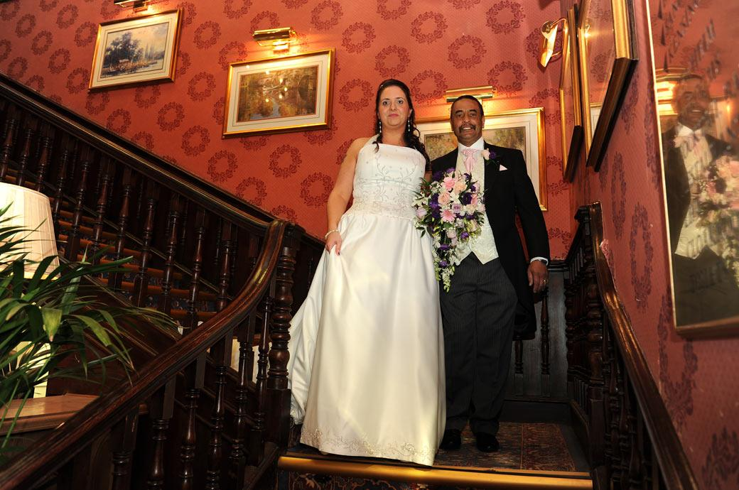 Smiling Bride walking down the stairs with her proud father in this wedding picture taken as walk down to The Blenheim Suite ceremony room at Coulsdon Manor Surrey