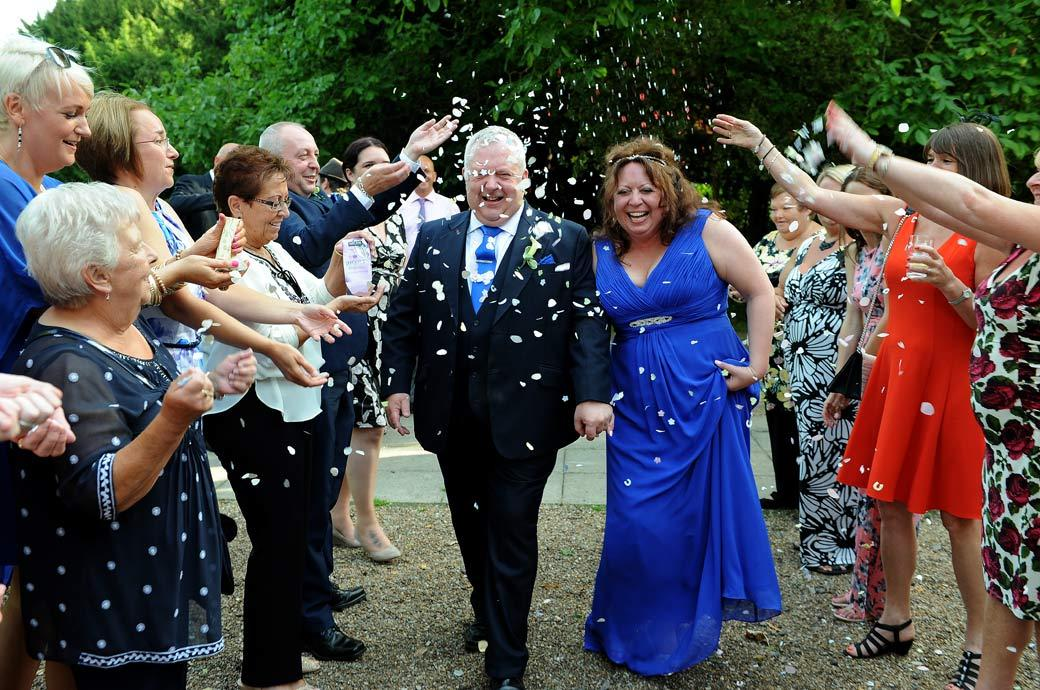 Confetti fun time for the newlyweds out in the courtyard captured in this wedding photo taken by Surrey Lane wedding photographers at Coulsdon Manor