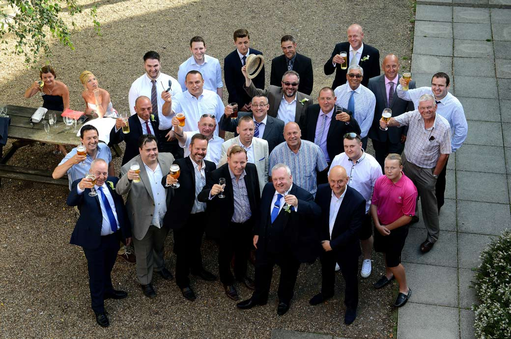 The Groom and gents raise a celebratory drink to the Surrey Lane wedding photographer taking a group wedding photo from the  roof of Coulsdon Manor in Surrey