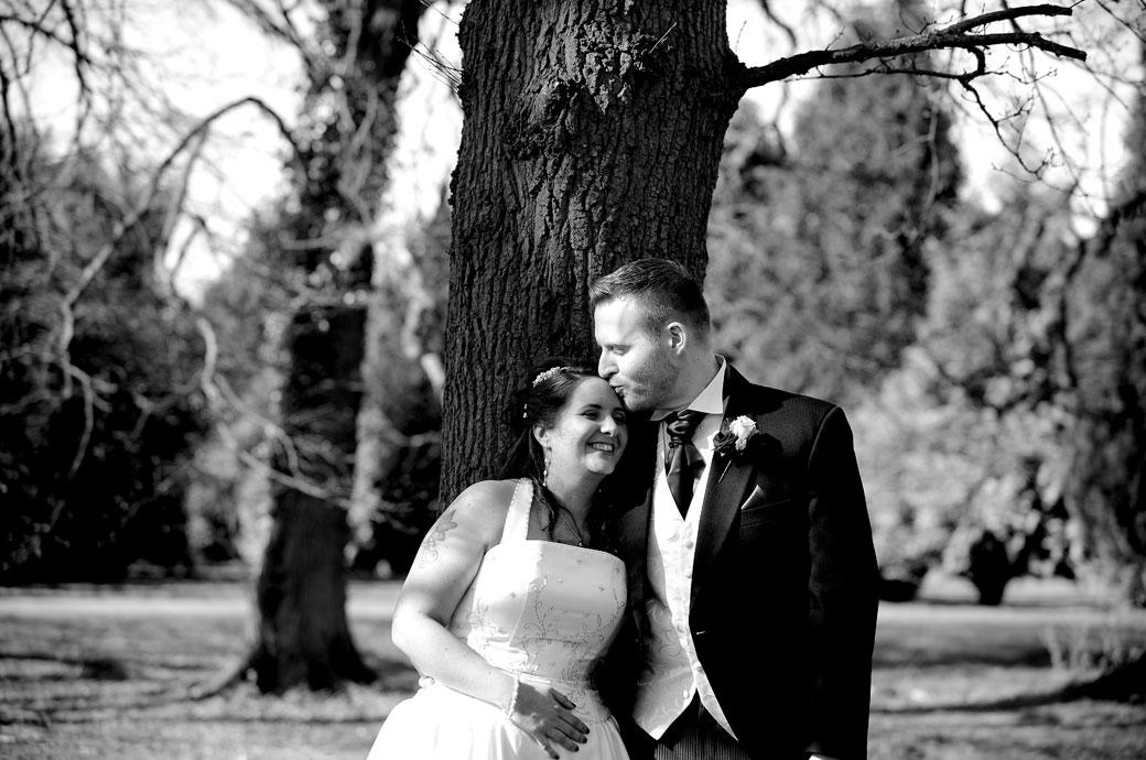Groom gives his wife a loving kiss on the head as they stand amongst the trees in this wedding picture taken in the lovely grounds of Coulsdon Manor Surrey wedding venue