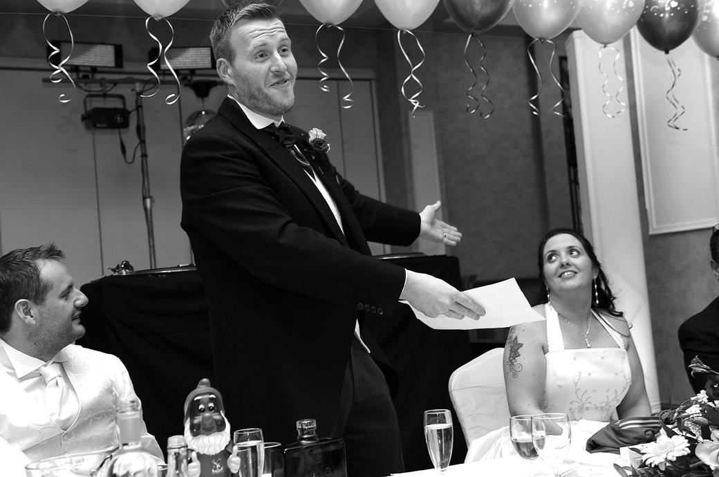 Groom captured in this wedding photo as he addresses his wife during the speeches taken in The Manor House Suite at Surrey wedding venue Coulsdon Manor
