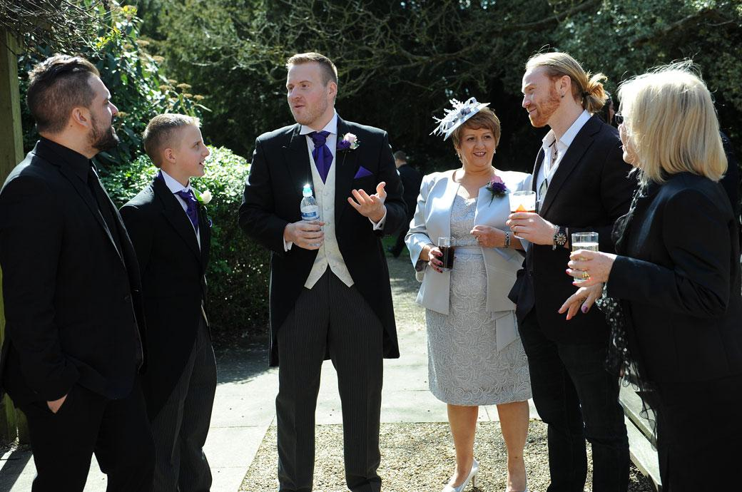 Groom deep in conversation with guests in this informal pre wedding picture taken in the Terrace area of popular wedding venue Coulsdon Manor in Surrey
