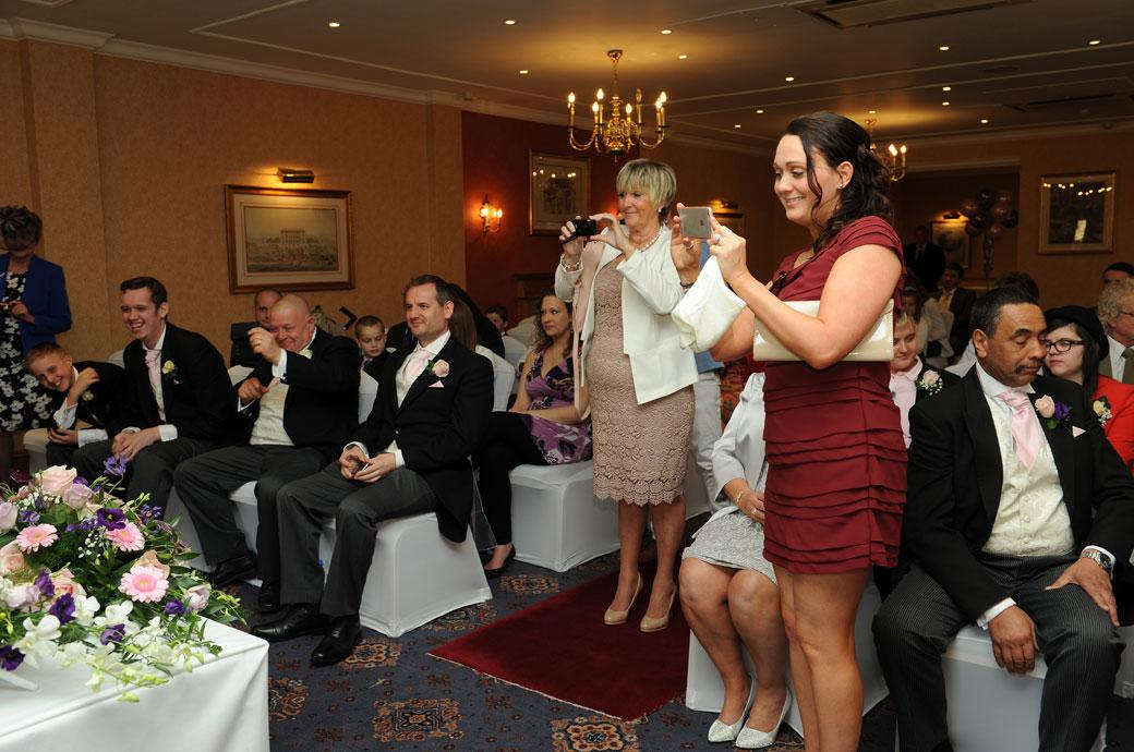 A wedding photograph of guests taking their own pictures of the newlyweds signing the marriage register in The Blenheim Suite at Coulsdon Manor Surrey