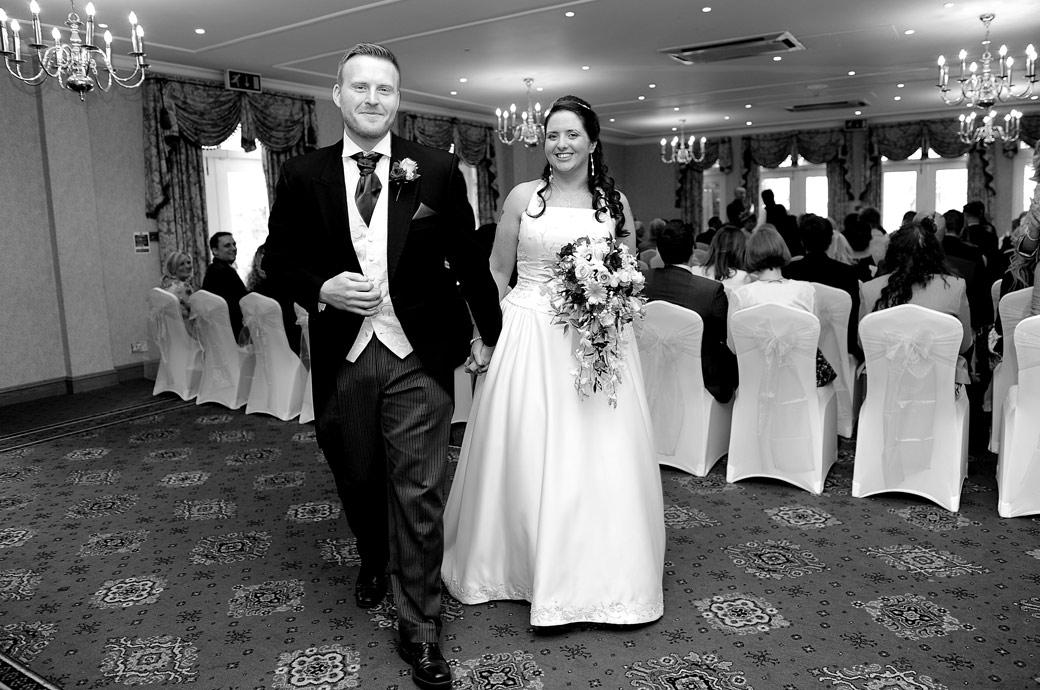 A very happy and smiling Bride and groom leave The Blenheim Suite at Coulsdon Manor in Surrey ready to celebrate their marriage in this lovely natural wedding picture