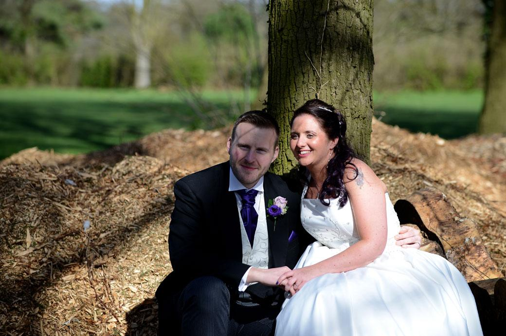 Smiling and content newlywed couple sitting down together in some tranquil woods in Surrey holding hands in this sweet wedding photograph by a Coulsdon Manor fairway