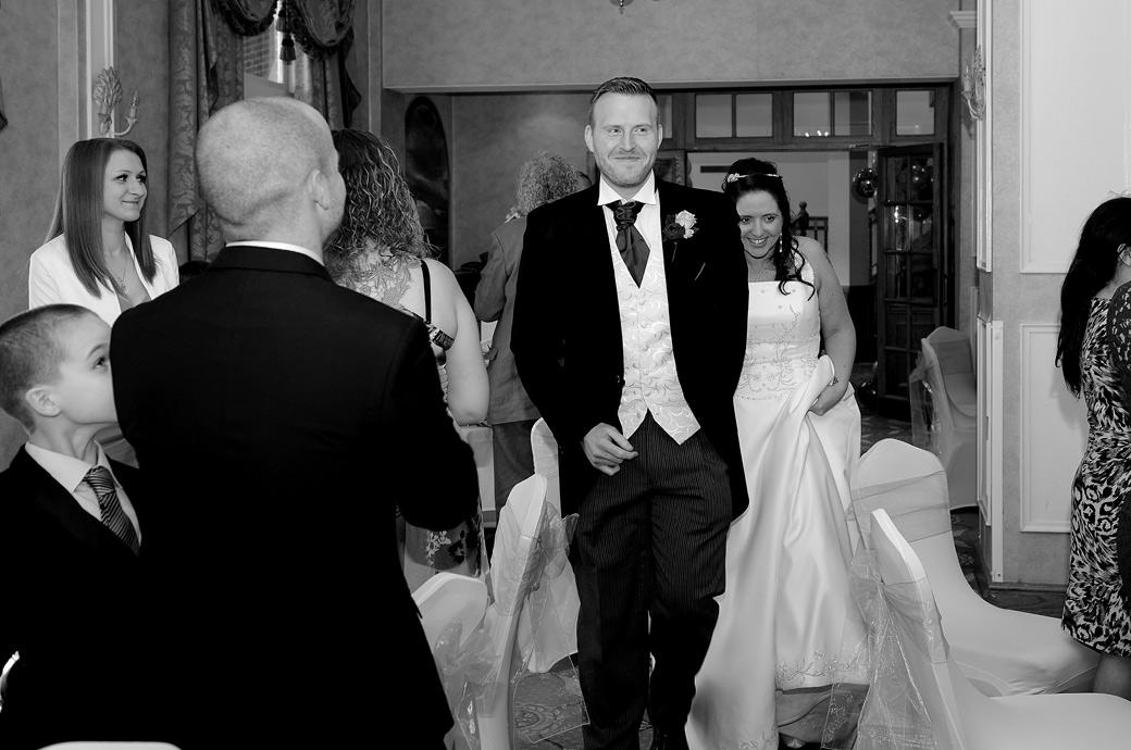 Happy smiling Bride and groom walk into The Manor House Suite to applauding guests for their wedding breakfast captured in this Coulsdon Manor wedding photograph