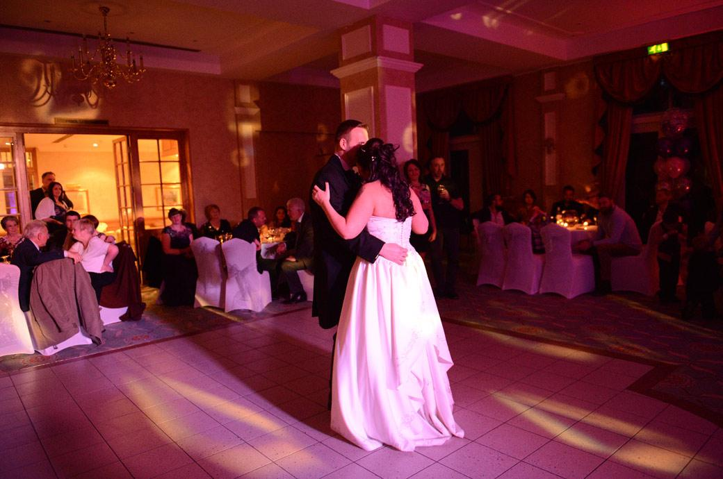 A romantic wedding picture of the newlywed couple having their first dance in The Manor House Suite at Coulsdon Manor in Surrey